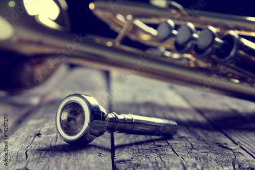 Fotografia Trumpet mouthpiece on an old wooden table. Vintage style.