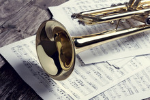 Trumpet And Sheet Music On Old Wooden Table. Vintage Style.