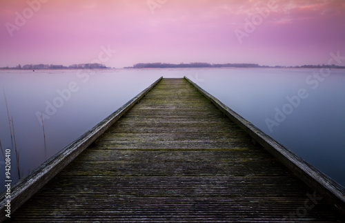 Fotobehang Purper Serene color image of a jetty in a lake