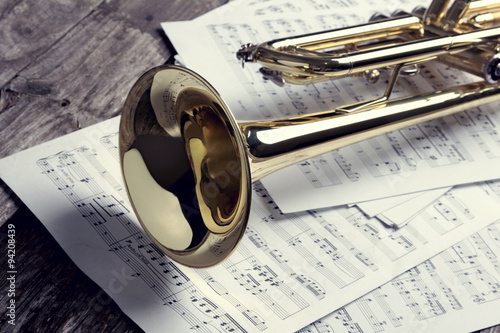 Trumpet and sheet music on old wooden table. Vintage style. Fototapet