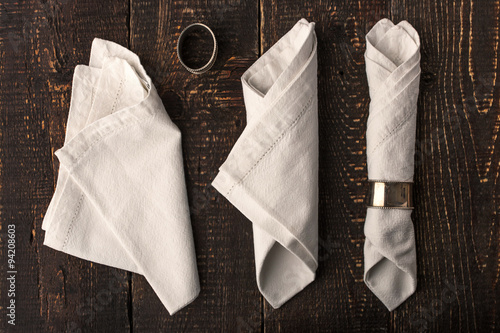 Fotografie, Obraz  Set of the napkins with vintage ring on the wooden table top view