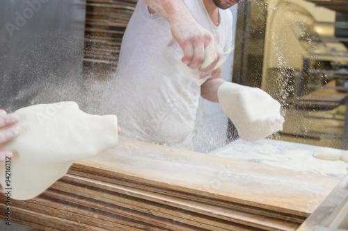 Cookers preparing pizza dough