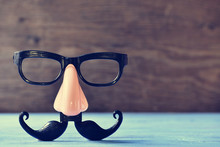 Fake Mustache, Nose And Eyeglasses On A Blue Surface