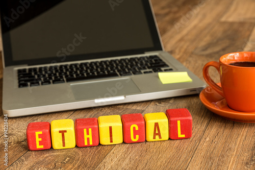 Fotografie, Obraz  Ethical written on a wooden cube in front of a laptop