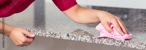 Fotografering Woman cleaning countertop