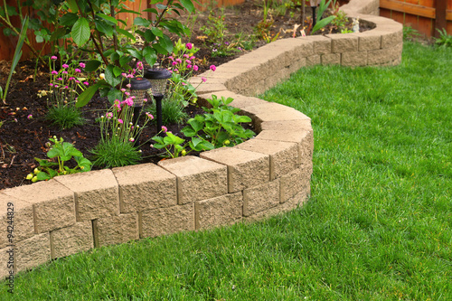 Recess Fitting Garden stone wall with perfect grass landscaping in garden with artificial grass