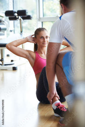 Spoed Foto op Canvas Fitness young sporty woman with trainer exercise in fitness gym