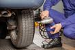 Mechanic Holding Pneumatic Wrench At Garage