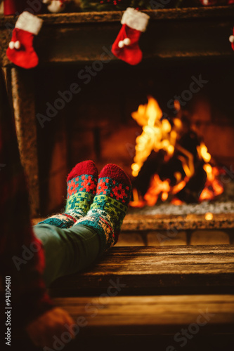 Deurstickers Ontspanning Feet in woollen socks by the fireplace. Woman relaxes by warm fire and warming up her feet in woollen socks. Close up on feet. Winter and Christmas holidays concept.