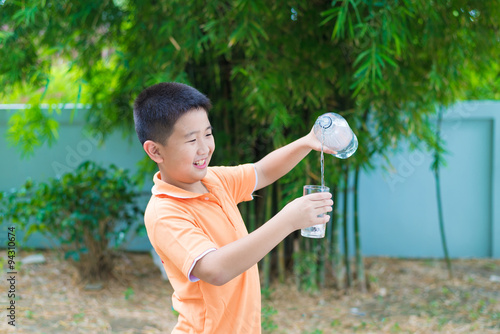 Fotografia  Asian boy pouring water into glass from bottle,