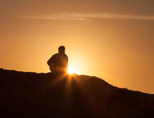 Silhouette Of Lone Man Sitting...