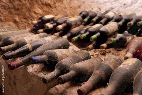 Fotografía  Botellas de vino viejos en un escalón de piedra, una cueva