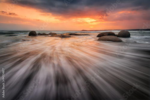 Fotobehang Grijs Sea sunrise. Stormy sea beach with slow shutter and waves flowing out
