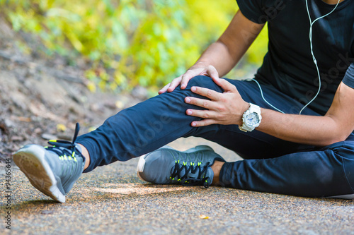 Fotografiet  Male athlete suffering from pain in leg while exercising
