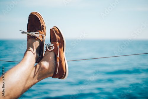 Photo of man legs on the yacht and wearing boat shoes