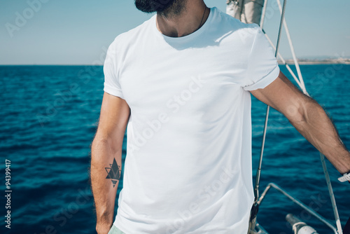 Photo of young bearded man standing on a yacht and looking at the horizon