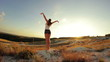 Young beautiful girl standing on a mountain at sunset hands raised