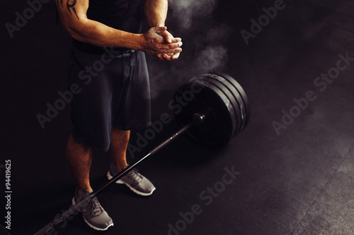 Fotografia  Athlete clapping hands with talc before deadlift barbells workout