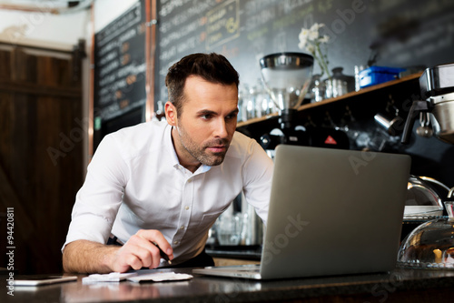 Photo  Restaurant manager working on laptop, counting small business income