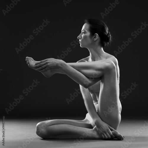 Nude yoga. Beautiful sexy body of young woman on black background