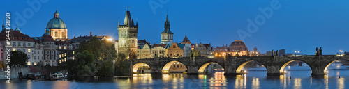Staande foto Praag Evening panorama of the Charles Bridge in Prague, Czech Republic, with dome of the Saint Francis of Assisi Church, Old Town Bridge Tower, Old Town Water Tower, dome of the National Theatre