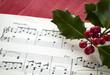 Notenblätter für Klavier und Ilex, Stechpalme mit roten Beeren