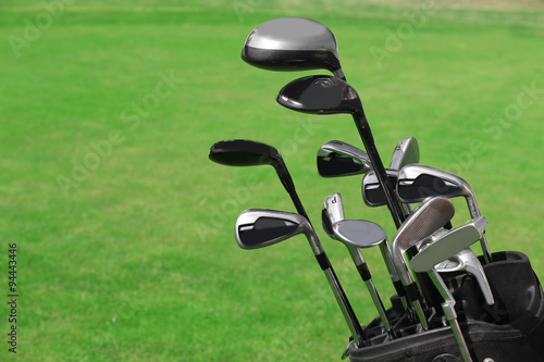 Deurstickers Golf Golf bag with clubs on green field, close up