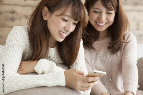 Fotografía  Two young women are seen together the smart phone on the sofa