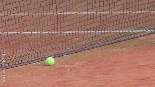 Gravel tennis court with tennis ball