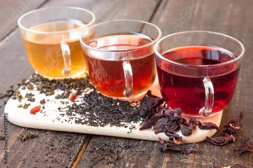 Staande foto Thee Three glass cups of tea on wooden boards
