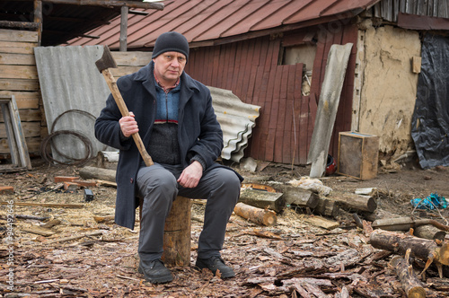 Mature man with an axe sitting on a log Canvas-taulu