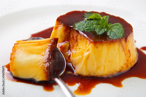 Poster Dessert Caramel custard pudding and spoon on plate with lemon balm leave on top
