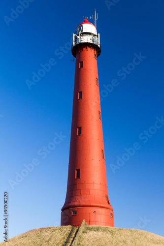 Montage in der Fensternische Leuchtturm Red lighthouse in Ijmuiden with a beautiful blue sky