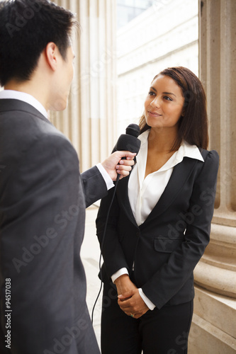Photo  A reporter interviews a well dressed woman