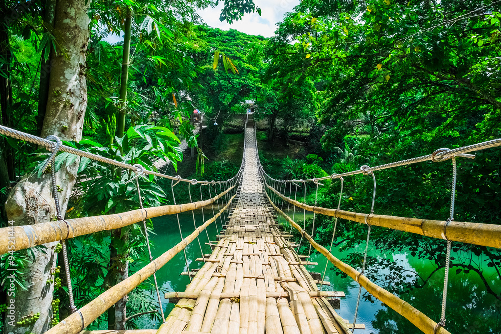 Fototapeta Bamboo pedestrian suspension bridge over river