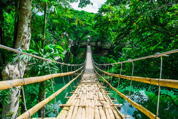 Obraz na Plexi Bamboo pedestrian suspension bridge over river