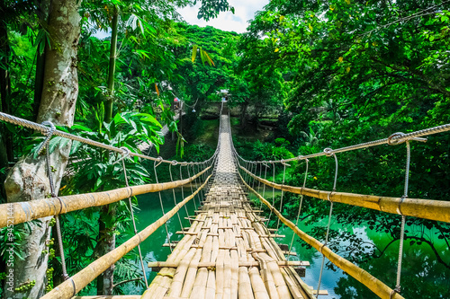 Tuinposter Bruggen Bamboo pedestrian suspension bridge over river