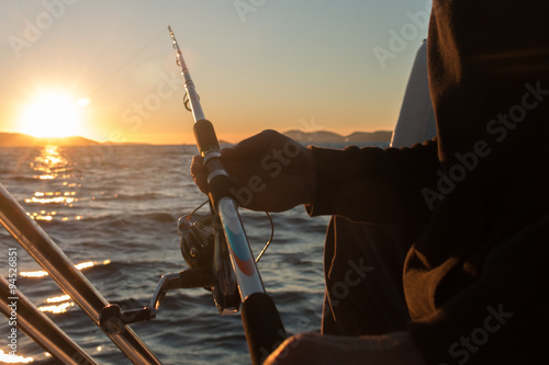 Printed kitchen splashbacks Fishing Man's hand with a fishing equipment in sunset