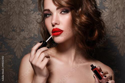 Fotografie, Obraz  Woman applying red lipstick