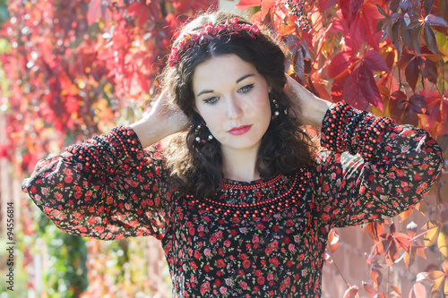 Fotografie, Obraz  Portrait of melancholy autumn girl with autumn wreath at red floral background o