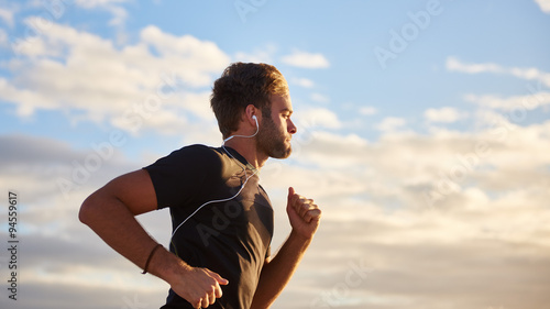 Man jogging on the beach with earphones