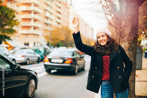 Fotografia, Obraz Happy young woman calling for a taxi in the city