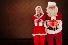 Composite Image Of Santa And Mrs Claus Holding Gifts