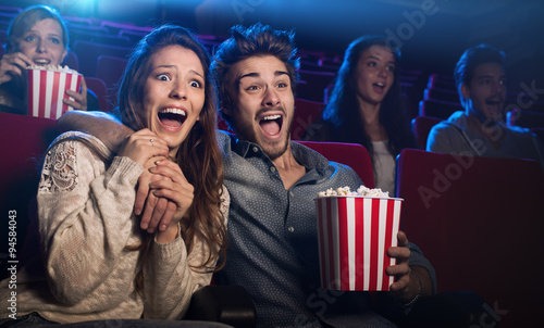 Photo  Young couple at the cinema watching an horror movie