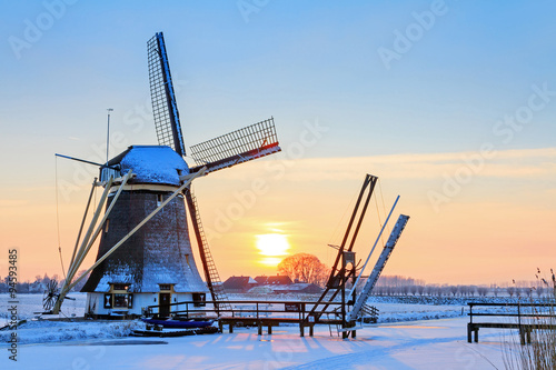 Photo sur Toile Moulins Beautiful sunset behind an old mill in winter in the Netherlands
