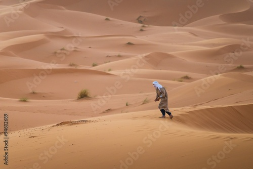 Fotografering  a touareg walking in the desert