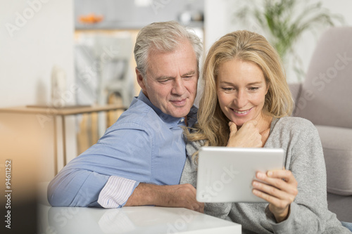 Fotografia  Mature couple sitting in sofa and using tablet pc