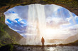 Leinwanddruck Bild - incredible waterfall in Iceland, silhouette of man enjoying amazing view of nature