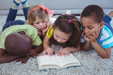 Happy Multi-ethnic Kids Reading A Book Together