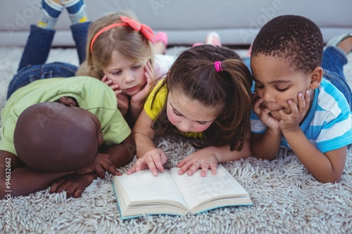 Fototapeta Happy kids reading a book together